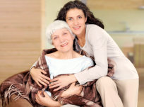 daughter hugging her elderly mother with a smile