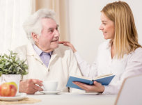 elderly man having a cup of tea while talking from a caregiver