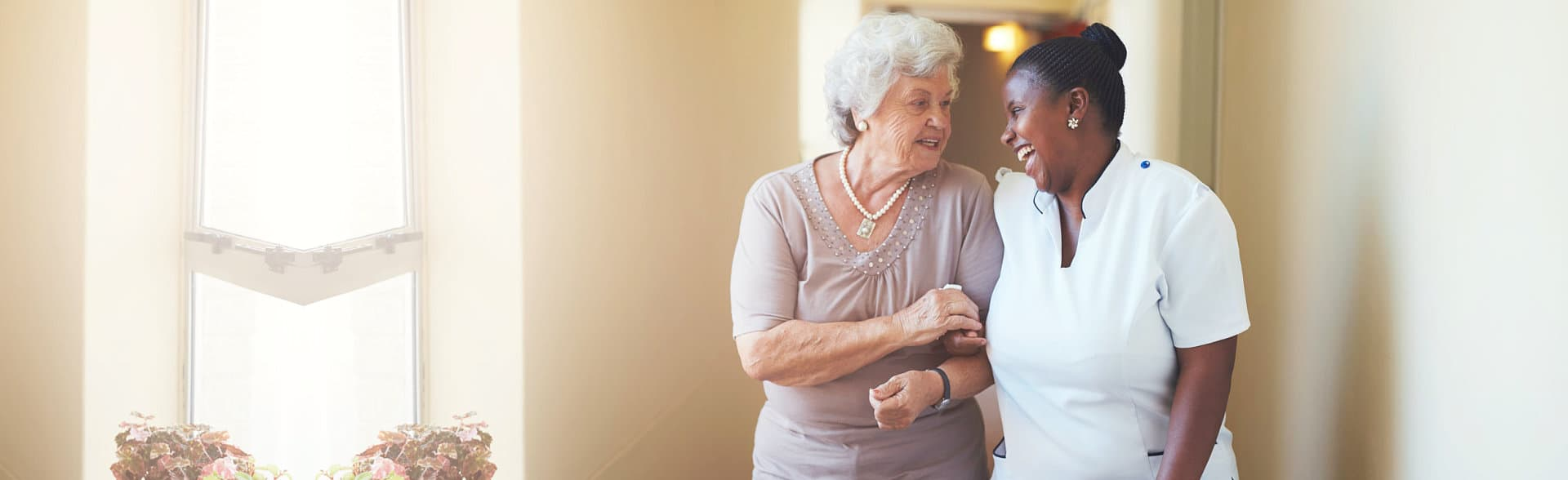 elderly woman and caregiver talking while walking happily