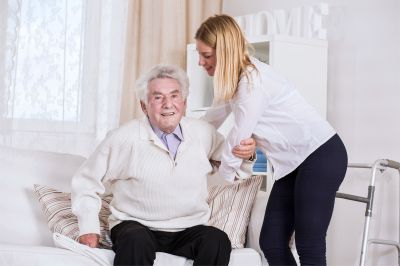 young female care assistant helping senior man