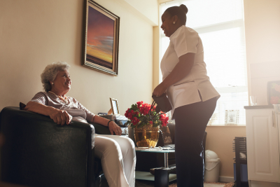 senior woman sitting on a chair at home with female caregiver standing by